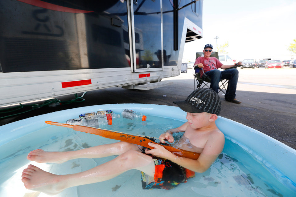 Photo -  Cactus Barnes, 6, plays in a swimming pool as his big brother, Cutter Barnes,15, looks on during the International Finals Youth Rodeo at the Heart of Oklahoma Expo Center in Shawnee, Monday July 8, 2013. The Barnes' are from Maybell, Colorado, and set the pool up next to their horse trailer. Photo By Steve Gooch, The Oklahoman