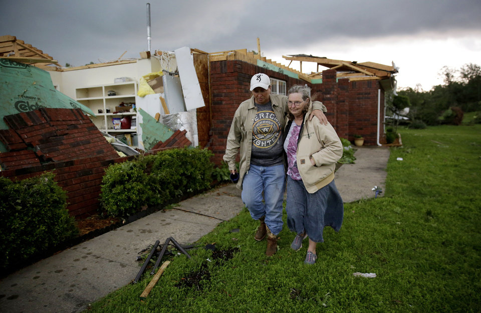 Photo - Karen Spencer is helped to her storm cellar by her daughter Tammi Foster in Peggs, Ok. Tuesday, May 21, 2019. Spencer's home was hit by an apparent tornado on Monday night. She and her husband Ed didn't have time to make it to the cellar on Monday and rode the storm out in their home. (Mike Simons/Tulsa World/Tulsa World via AP)