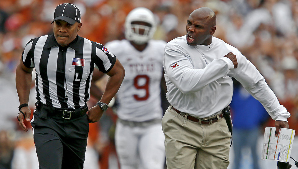 Photo - Texas coach Charlie Strong argues with line judge Kevin Vicknair after a holding call on Texas  the Red River Showdown college football game between the University of Oklahoma Sooners (OU) and the University of Texas Longhorns (UT) at the Cotton Bowl in Dallas on Saturday, Oct. 11, 2014. 