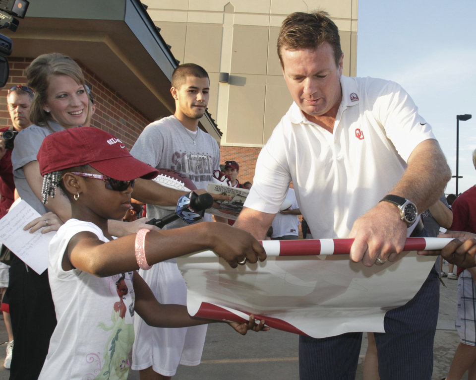 Photo - OU head coach Bob Stoops gives fans an early autograph at 7 a.m. as he and five players sign autographs at the entrance gate as the University of Oklahoma college football teams holds media/fan appreciation day on Friday, August 6, 2010, in Norman, Okla.  Essence Robinson, 5, from Joplin, Mo. gets a poster signed. Photo by Steve Sisney, The Oklahoman ORG XMIT: KOD