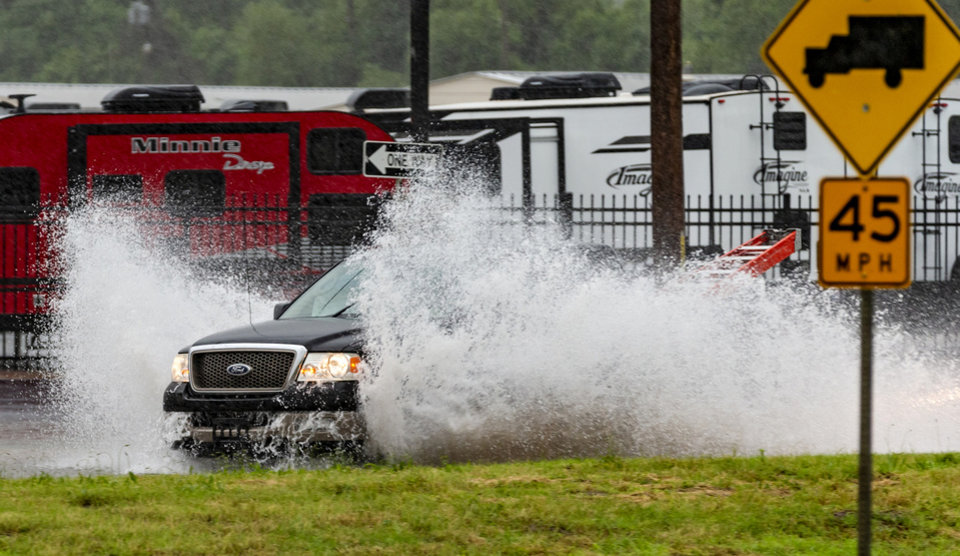 Photo - Traffic makes its way through flash flood waters near Rockwell Ave. and Reno Ave. in Oklahoma City, Okla. on Thursday, June 6, 2019. [Chris Landsberger/The Oklahoman]