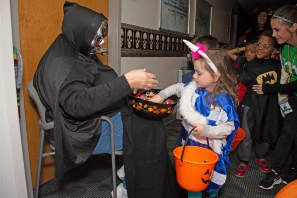 Photo -  Kids line up to get treats during a halloween event at Oklahoma Medical Research Foundation. [PROVIDED]