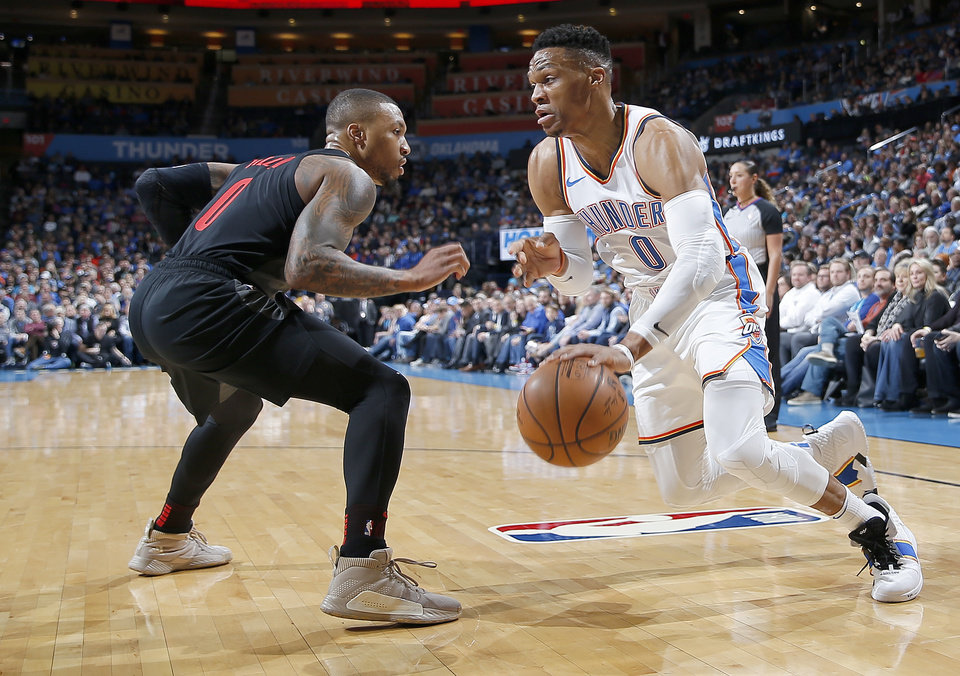 Photo - Oklahoma City's Russell Westbrook (0) drives to the basket as Portland's Damian Lillard (0) defends during the NBA basketball game between the Oklahoma City Thunder and the Portland Trail Blazers at Chesapeake Energy Arena in Oklahoma City, Tuesday, Jan. 22, 2019. Photo by Sarah Phipps, The Oklahoman
