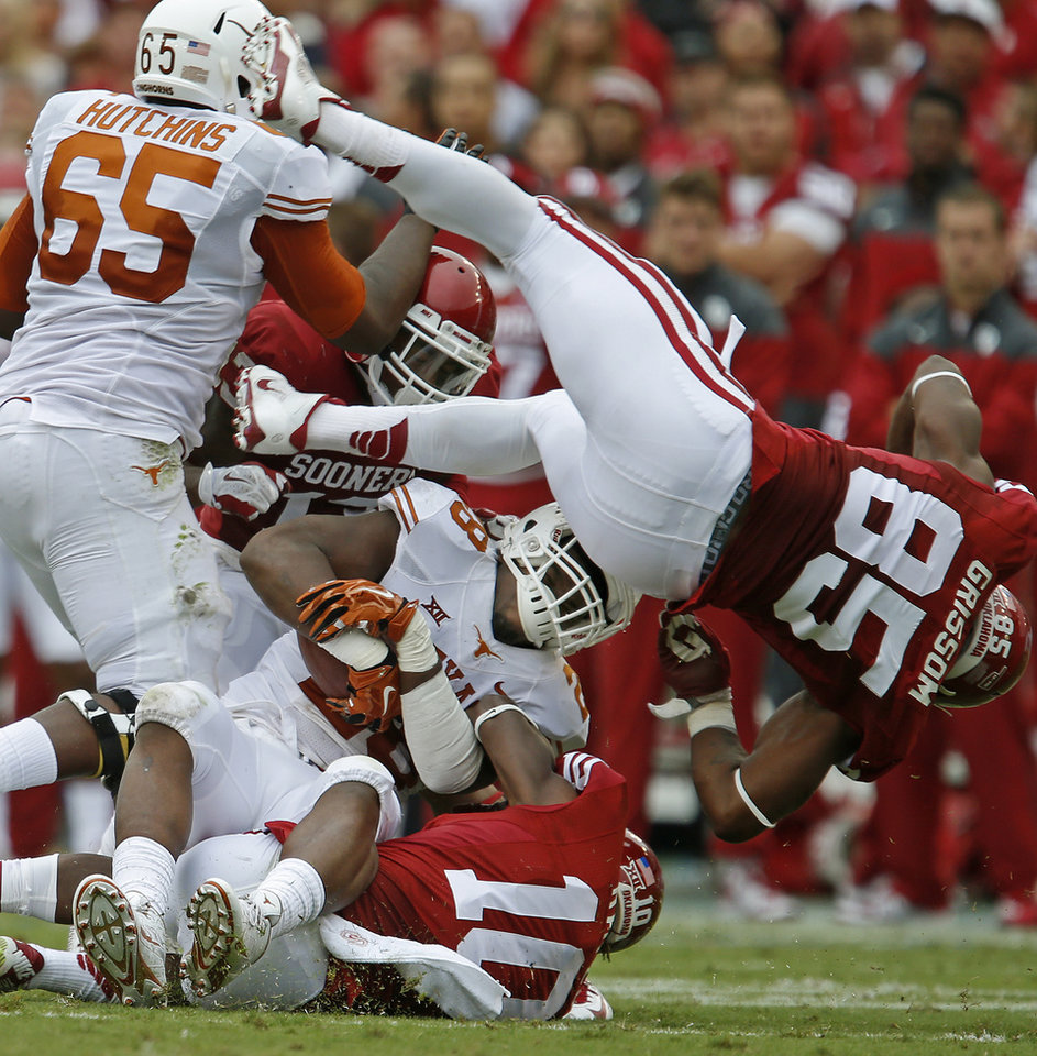 Photo - Oklahoma's Quentin Hayes (10) and Geneo Grissom (85) bring down Texas' Malcolm Brown (28) during the Red River Showdown college football game between the University of Oklahoma Sooners (OU) and the University of Texas Longhorns (UT) at the Cotton Bowl in Dallas on Saturday, Oct. 11, 2014. 