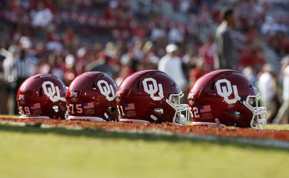 Photo - OU helmets sit on the field as players warm up before a college football game between the Oklahoma Sooners (OU) and South Dakota Coyotes at Gaylord Family - Oklahoma Memorial Stadium in Norman, Okla., Saturday, Sept. 7, 2019. [Nate Billings/The Oklahoman]