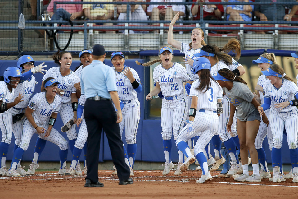 Photo - UCLA's Briana Perez is greeted at home after hitting a home run in the first inning of the second NCAA softball game in the championship series of the Women's College World Series between Oklahoma and UCLA at USA Softball Hall of Fame Stadium in Oklahoma City, Tuesday, June 4, 2019. [Bryan Terry/The Oklahoman]