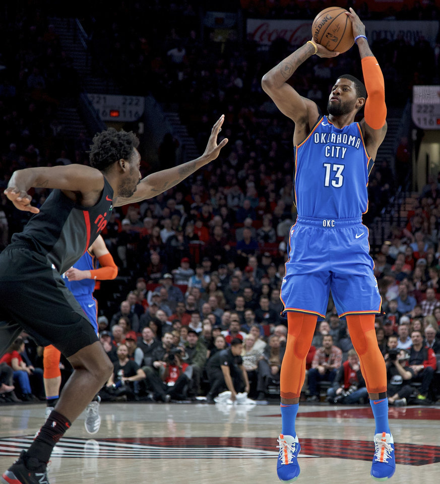 Photo - Oklahoma City Thunder forward Paul George, right, shoots over Portland Trail Blazers forward Al-Farouq Aminu during the first half of an NBA basketball game in Portland, Ore., Thursday, March 7, 2019. (AP Photo/Craig Mitchelldyer)