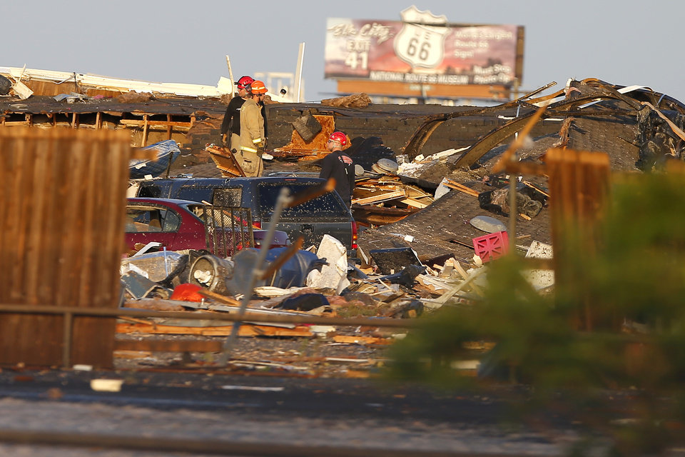 Photo - Workers looks through tornado damage  near the American Budget Value Inn in El Reno, Okla., Sunday, May 26, 2019. [Bryan Terry/The Oklahoman]