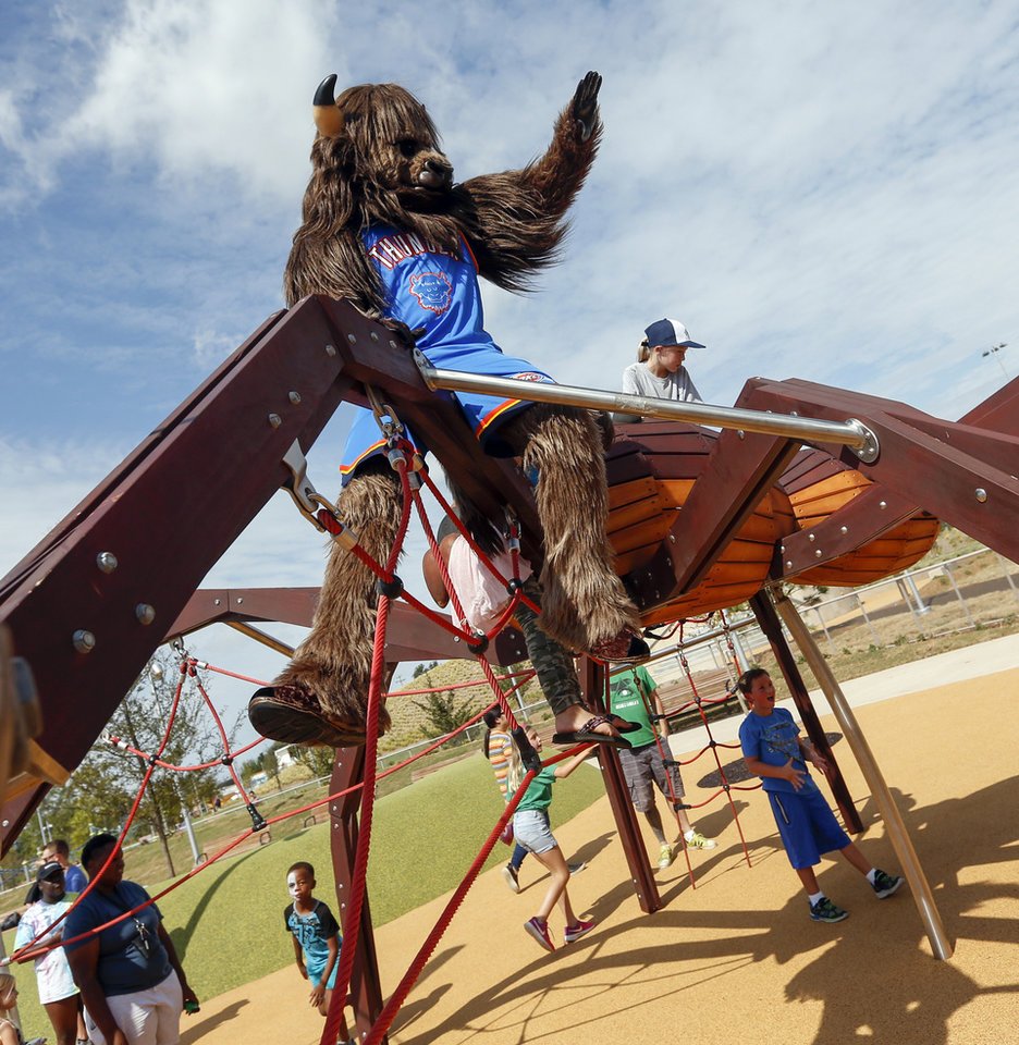Photo - Thunder mascot Rumble the Bison waves while visiting the children's playground during the grand opening weekend of Scissortail Park in Oklahoma City, Saturday, Sept. 28, 2019. [Nate Billings/The Oklahoman]