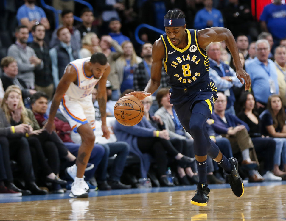 Photo - Indiana's Justin Holiday (8) dribbles the ball after stealing an inbounds pass by Oklahoma City's Terrance Ferguson (23), left, late in the fourth quarter during an NBA basketball game between the Indiana Pacers and the Oklahoma City Thunder at Chesapeake Energy Arena in Oklahoma City, Wednesday, Dec. 4, 2019. Indiana won 107-100. [Nate Billings/The Oklahoman]