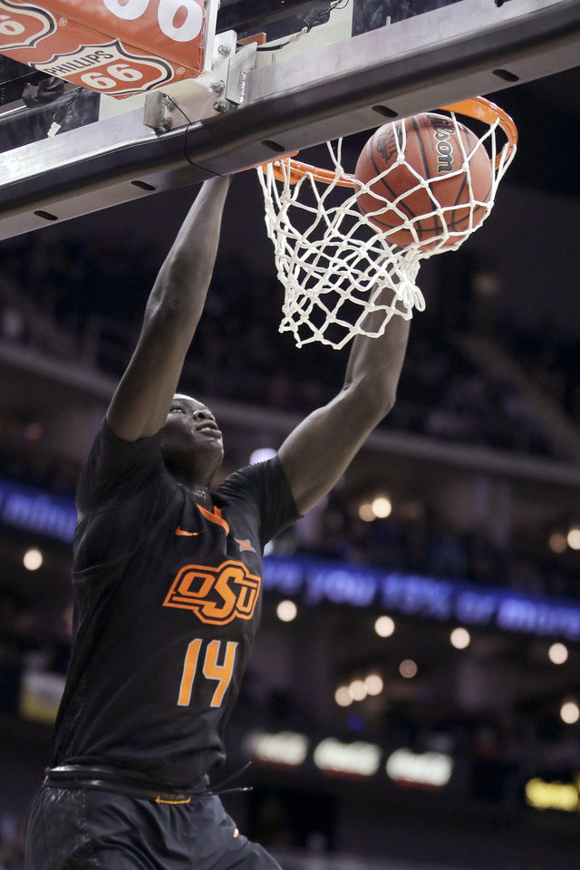 Photo - Oklahoma State's Yor Anei dunks during the first half of an NCAA college basketball game against TCU in the Big 12 men's tournament Wednesday, March 13, 2019, in Kansas City, Mo. (AP Photo/Charlie Riedel)