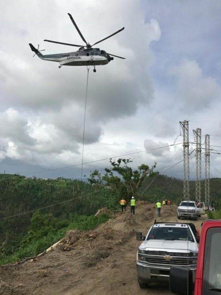 Photo -  A helicopter in 2018 supports a line being attached to a transmission pole in Puerto Rico. [PROVIDED]