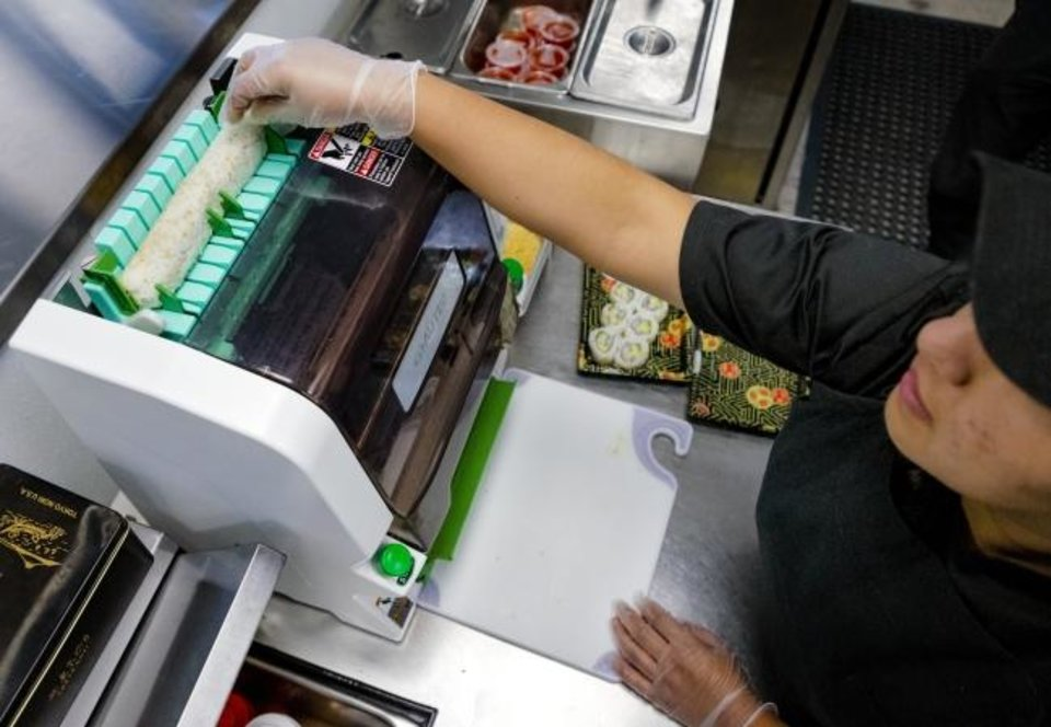 Photo -  Employee Julie Lopez uses an automated Sushi Cutter as she makes a sushi roll at the new Nhinjo Sushi-Grill located at 12301 S Western Ave. on Tuesday. The restaurant is a new franchise model launched by Nhinja Sushi & Wok.  [Chris Landsberger/The Oklahoman]