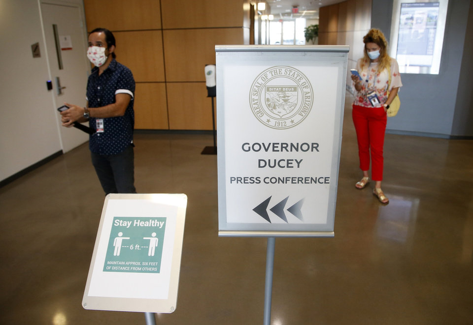 Photo -  Members of the media wait to be escorted to a briefing room to hear Arizona Republican Gov. Doug Ducey speak about the latest Arizona coronavirus data at a news conference Thursday, June 25, 2020, in Phoenix. (AP Photo/Ross D. Franklin, Pool)