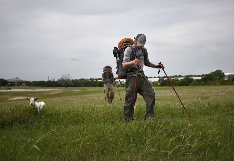 Photo - Phillip Aldrich, front, and Kyle Townsend  walk with Wrigley the goat walk in a field along Wilshire Boulevard in Oklahoma City,Thursday, April 19, 2012. The groups is walking with a a goat  to
