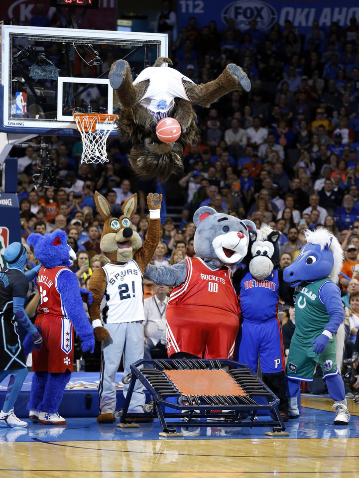 Photo - Thunder mascot Rumble performs with other costumed mascots in the first half of an NBA basketball game where the Oklahoma City Thunder play the Indiana Pacers at the Chesapeake Energy Arena in Oklahoma City, on Feb. 19, 2016.  Photo by Steve Sisney The Oklahoman