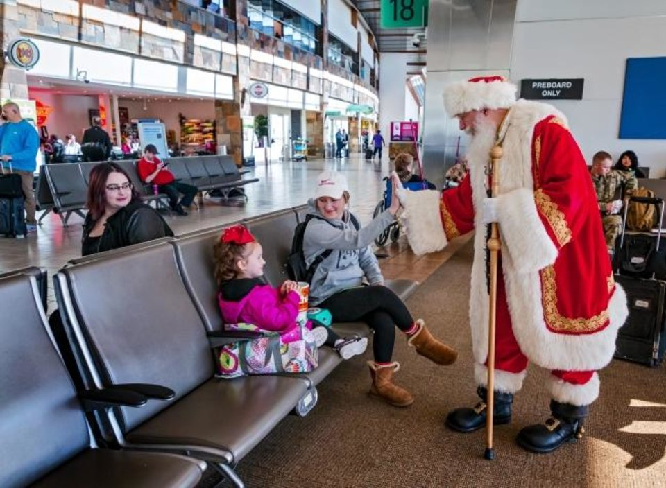 Photo -  Santa Claus gives a high five to Courtney LaRose and her daughter Mardi, 4, as they wait to catch a flight Thursday at Will Rogers World Airport in Oklahoma City. [Chris Landsberger/The Oklahoman]
