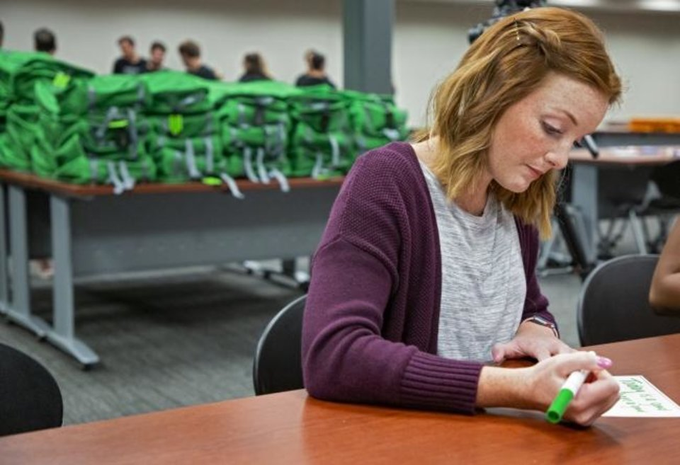 Photo -  Paycom's Abbi Moulton on Friday fills out a personalized card to be put in a backpack along with school supplies at Paycom. [CHRIS LANDSBERGER/THE OKLAHOMAN]