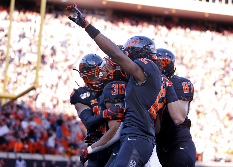 Photo - Oklahoma State celebrates a 92-yard touchdown run by Chuba Hubbard (30) in the third quarter during the college football game between the Oklahoma State University Cowboys and the TCU Horned Frogs at Boone Pickens Stadium in Stillwater, Okla.,  Saturday, Nov. 2, 2019. OSU won 34-27. [Sarah Phipps/The Oklahoman]