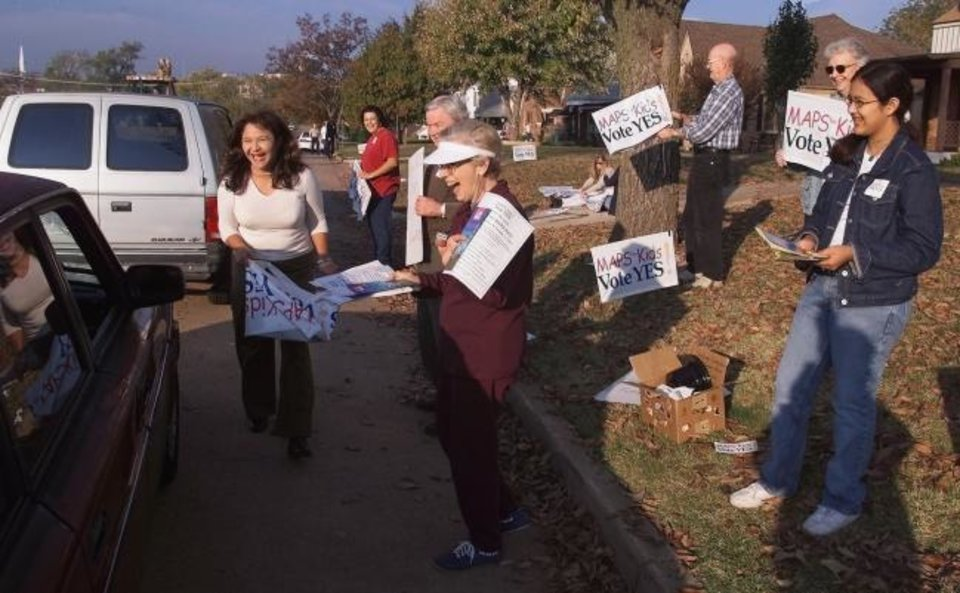 Photo -  A small group of Cleveland Elementary moms, grandparents and friends hand out stickers, brochures and yard signs supporting the MAPS for Kids proposal to parents dropping their children off at the northwest Oklahoma City school. [The Oklahoman Archives]