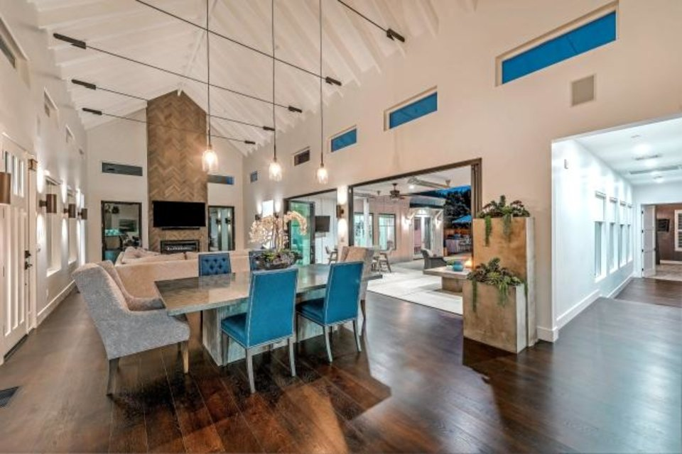 Photo -  HGTV star Tarek El Moussa and new girlfriend Heather Rae Young cleaned up in the sale of their Costa Mesa, California, home, which sold for $130,000 over asking.  The modern farmhouse features cathedral-style ceilings, a floor-to-ceiling fireplace and a gleaming chef's kitchen. Pocketing walls of glass open directly to the swimming pool. [TNS PHOTO]
