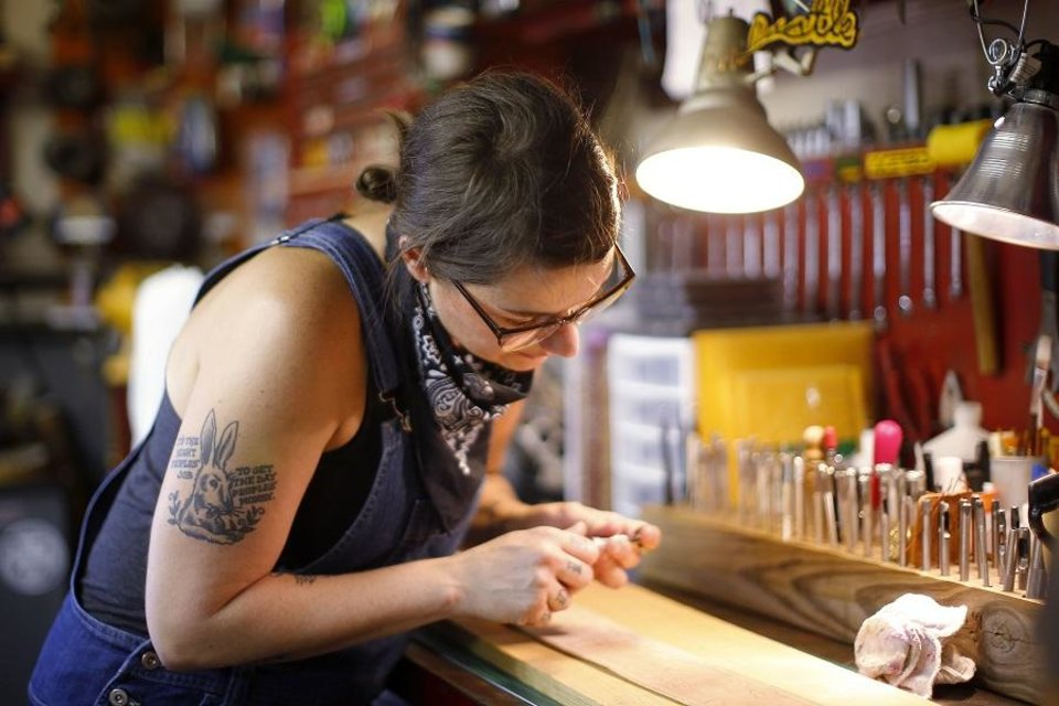 Photo - Ali Harter-Street works on a leather guitar strap inside her shop in Oklahoma City, Friday, Aug. 9, 2019. [Bryan Terry/The Oklahoman]