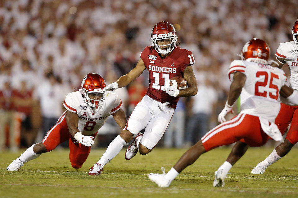 Photo - Oklahoma's Jadon Haselwood (11) runs past Houston's Chandler Smith (8) during a college football game between the University of Oklahoma Sooners (OU) and the Houston Cougars at Gaylord Family-Oklahoma Memorial Stadium in Norman, Okla., Sunday, Sept. 1, 2019. Oklahoma won 49-31. [Bryan Terry/The Oklahoman]