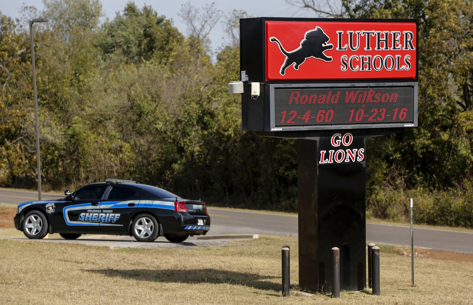 Photo -  An Oklahoma County sheriff's car is parked Friday outside the Luther Public Schools auditorium, part of the added security for the funeral of Ronald and Valerie Kay Wilkson. [Photo by Chris Landsberger, The Oklahoman]