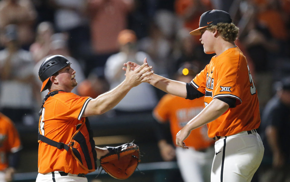 Photo - Colin Simpson (24) celebrates with Peyton Battenfield (55) following the Oklahoma City Regional NCAA baseball game between Oklahoma State University (OSU) and UConn at Chickasaw Bricktown Ballpark in Oklahoma City,  Monday, June 3, 2019. [Sarah Phipps/The Oklahoman]