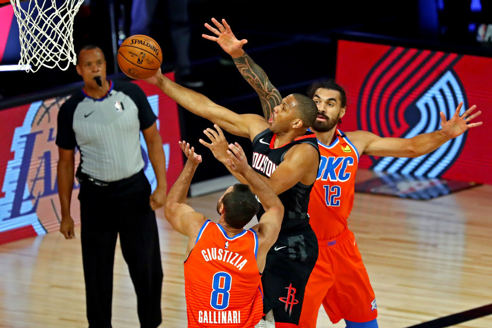 Photo - Aug 29, 2020; Lake Buena Vista, Florida, USA; Houston Rockets guard Eric Gordon (10) shoots the ball against Oklahoma City Thunder forward Danilo Gallinari (8) and center Steven Adams (12) during the first quarter in game five of the first round of the 2020 NBA Playoffs at The Field House. Mandatory Credit: Kim Klement-USA TODAY Sports
