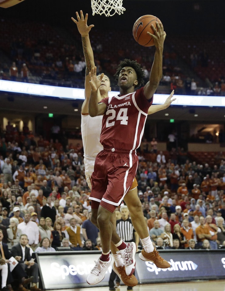 Photo - Oklahoma guard Jamal Bieniemy (24) scores past Texas forward Kamaka Hepa (33) during the first half of an NCAA college basketball game in Austin, Texas, Wednesday, Jan. 8, 2020. (AP Photo/Eric Gay)
