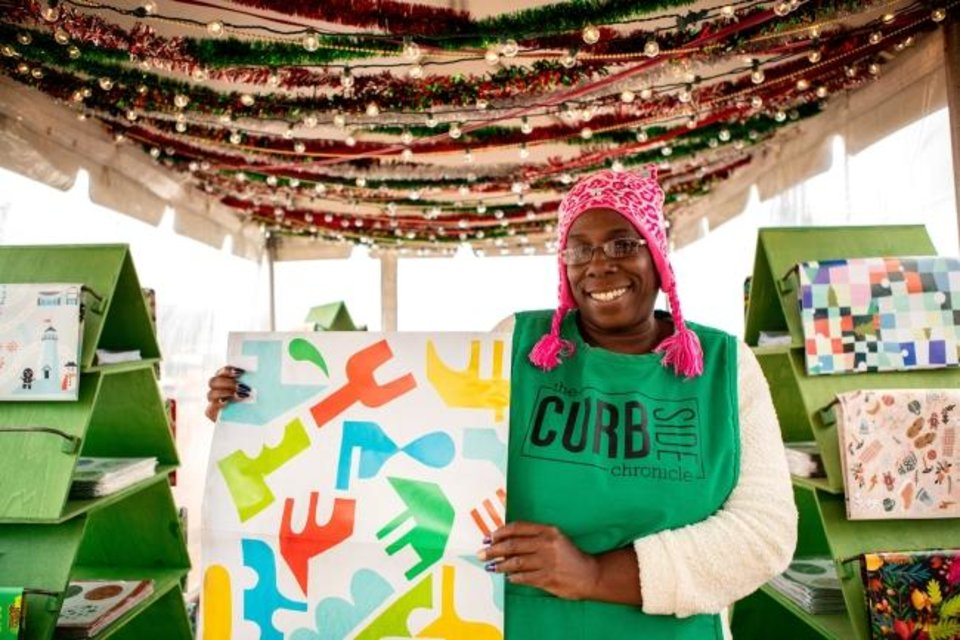 Photo -  Curbside Chronicle vendor Tee poses with some of this year's holiday wrapping paper. [PROVIDED]