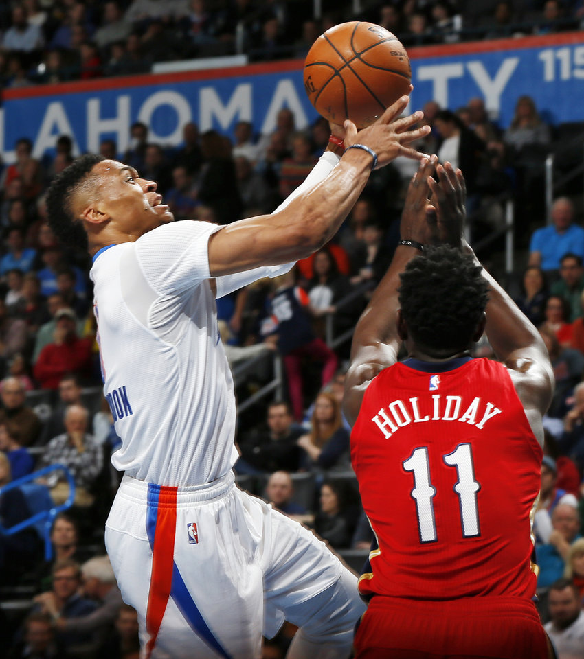 Photo - Oklahoma City's Russell Westbrook (0) tries to score against New Orleans' Jrue Holiday (11) during an NBA basketball game between the New Orleans Pelicans and the Oklahoma City Thunder at Chesapeake Energy Arena in Oklahoma City, Thursday, Feb. 11, 2016.  Photo by Nate Billings, The Oklahoman