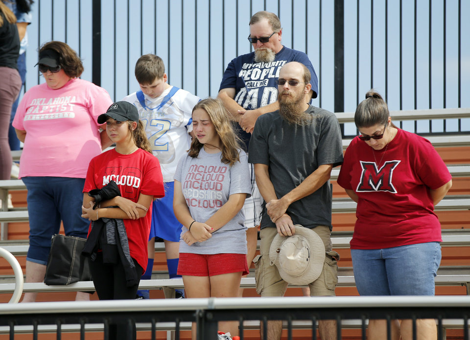 Photo -  McLoud fans stand Saturday for a moment of silence honoring Kaylen Thomas before the high school football game at O'Dell Field in Cushing. The game was postponed Friday and moved from McLoud after Thomas, a McLoud High School student, died Friday from a gunshot wound. [Photo by Nate Billings, The Oklahoman]