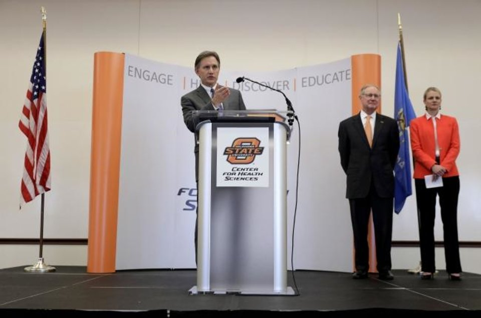 Photo -  Attorney General Mike Hunter speaks about a $270 million settlement with Purdue Pharma for opioid abuse in the state Tuesday, March 26, 2019. Listening OSU Center for Health Sciences President Dr. Kayse Shrum and OSU President Burns Hargis  [MIKE SIMONS/Tulsa World]