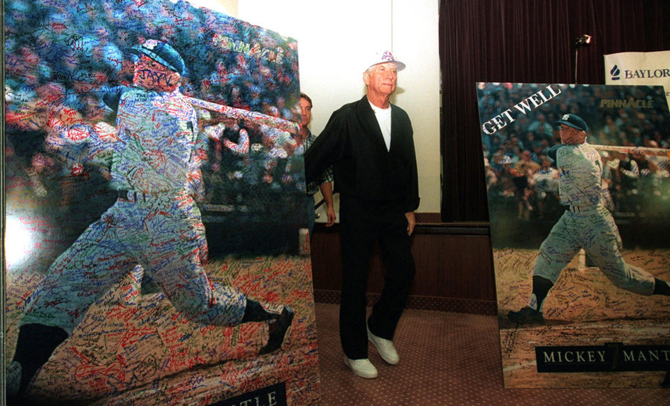 Photo - Baseball Hall of Famer Mickey Mantle walks between large get well signs, signed by fans, as he arrives at Baylor University Medical Center in Dallas, July 11, 1995, for a news conference.  Mantle continues to recover from his June 8th liver transplant. (AP Photo/Eric Gay)
