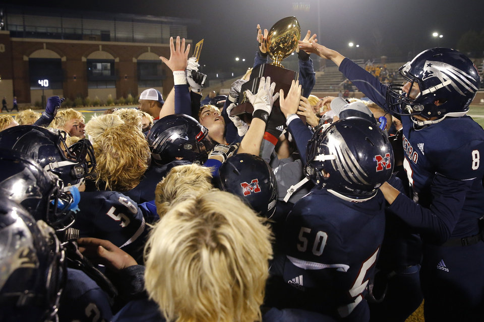 Photo - Tulsa Metro Christian celebrates with the trophy after the Class 2A football state championship game between Tulsa Metro Christian and Vian at Wantland Stadium in Edmond, Okla., Saturday, Dec. 14, 2019. [Bryan Terry/The Oklahoman]