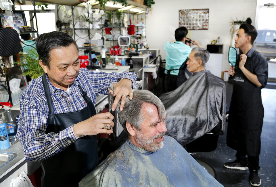 Photo -  Ky Nguyen, left, and his sons, Anh Thy Nguyen, center, and Dieu Thy Nguyen give haircuts to customers in the family's barber business, Hank's Barber Shop, on Tuesday.