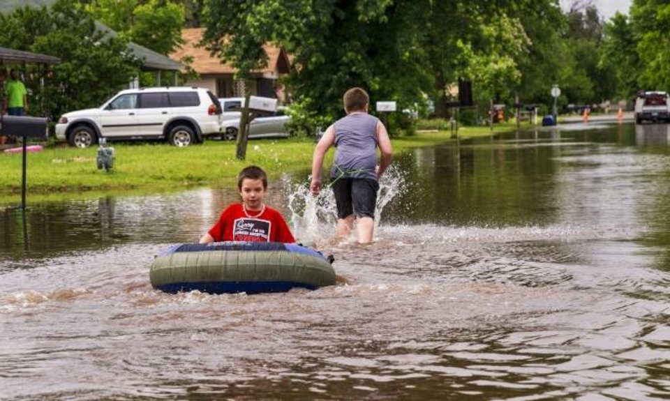 Photo -  Allik Reed pulls his brother Skyler through the water on a flooded street Tuesday after heavy rains flooded areas in El Reno. [Chris Landsberger/The Oklahoman]