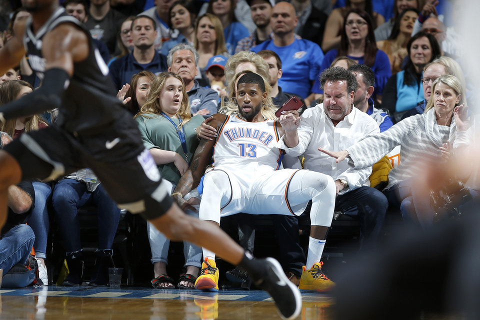 Photo - Oklahoma City's Paul George (13) falls into the crowd during an NBA basketball game between the Oklahoma City Thunder and the Sacramento Kings at Chesapeake Energy Arena in Oklahoma City, Saturday, Feb. 23, 2019. Sacramento won 119-116. Photo by Bryan Terry, The Oklahoman