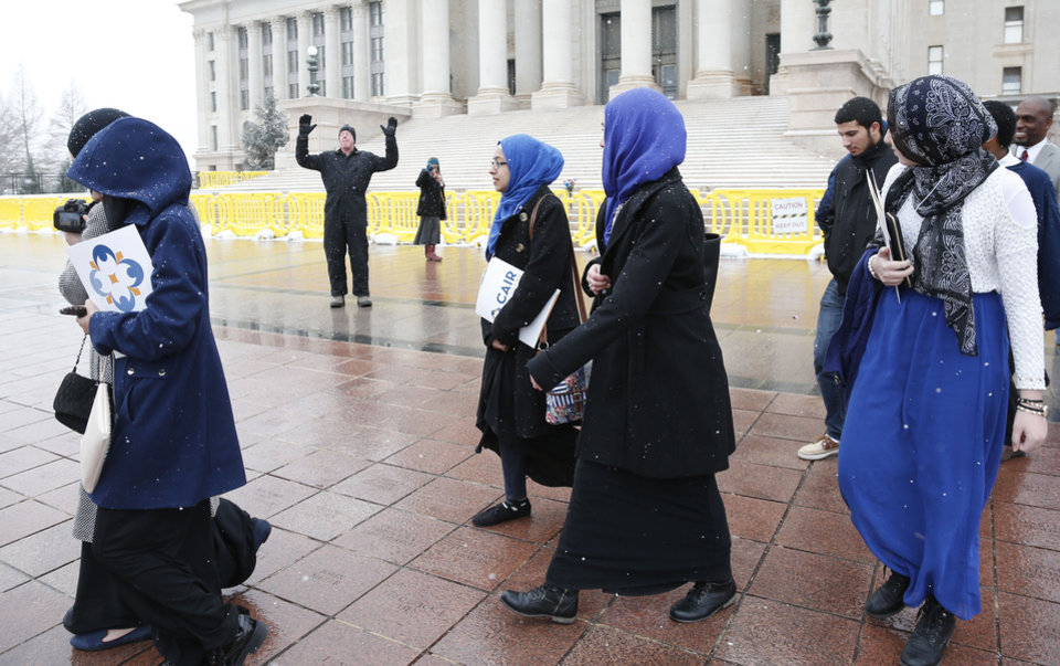 Photo - Participants from Muslim Day at the state Capitol walk past a solitary protestor as they leave following the program at the state Capitol in Oklahoma City, Friday, Feb. 27, 2015. (AP Photo/Sue Ogrocki)
