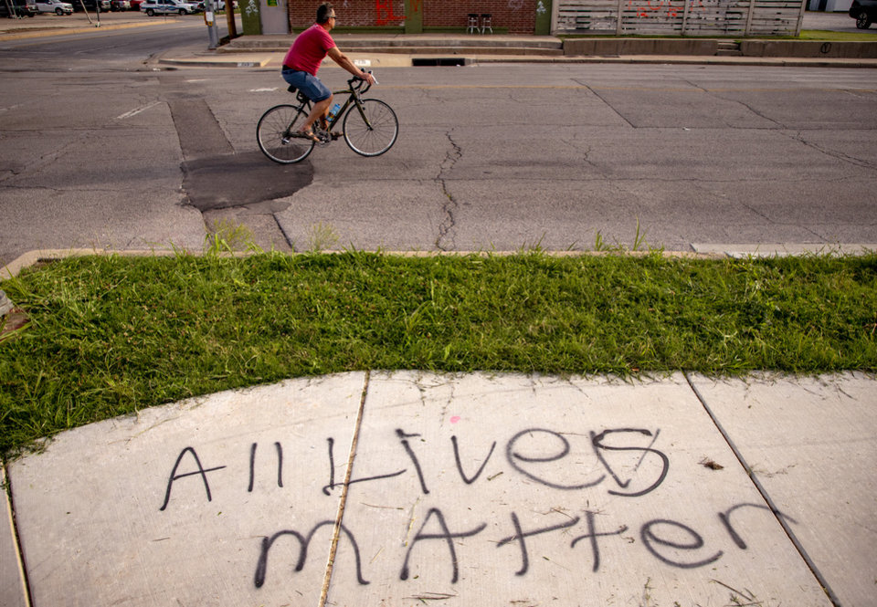 Photo - Graffiti on the sidewalk near NW 4th and Shartel Ave. on Monday, June 1, 2020, in Oklahoma City, Okla. that was left behind from the George Floyd protest on Sunday.   [Chris Landsberger/The Oklahoman]