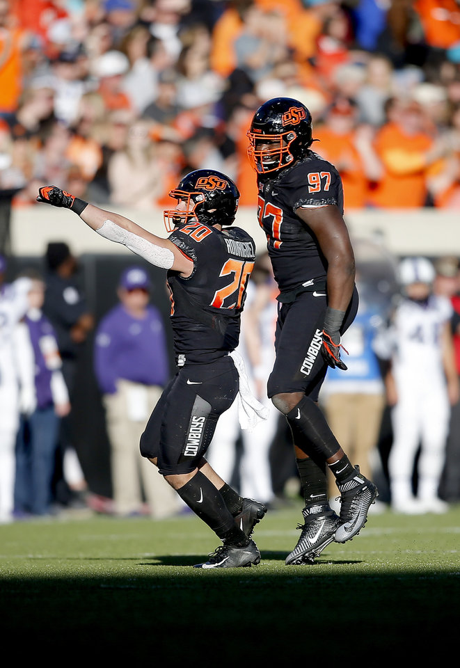 Photo - Oklahoma State's Malcolm Rodriguez (20) and Amadou Fofana (97) celebrate a play in the third quarter during the college football game between the Oklahoma State University Cowboys and the TCU Horned Frogs at Boone Pickens Stadium in Stillwater, Okla.,  Saturday, Nov. 2, 2019. OSU won 34-27. [Sarah Phipps/The Oklahoman]