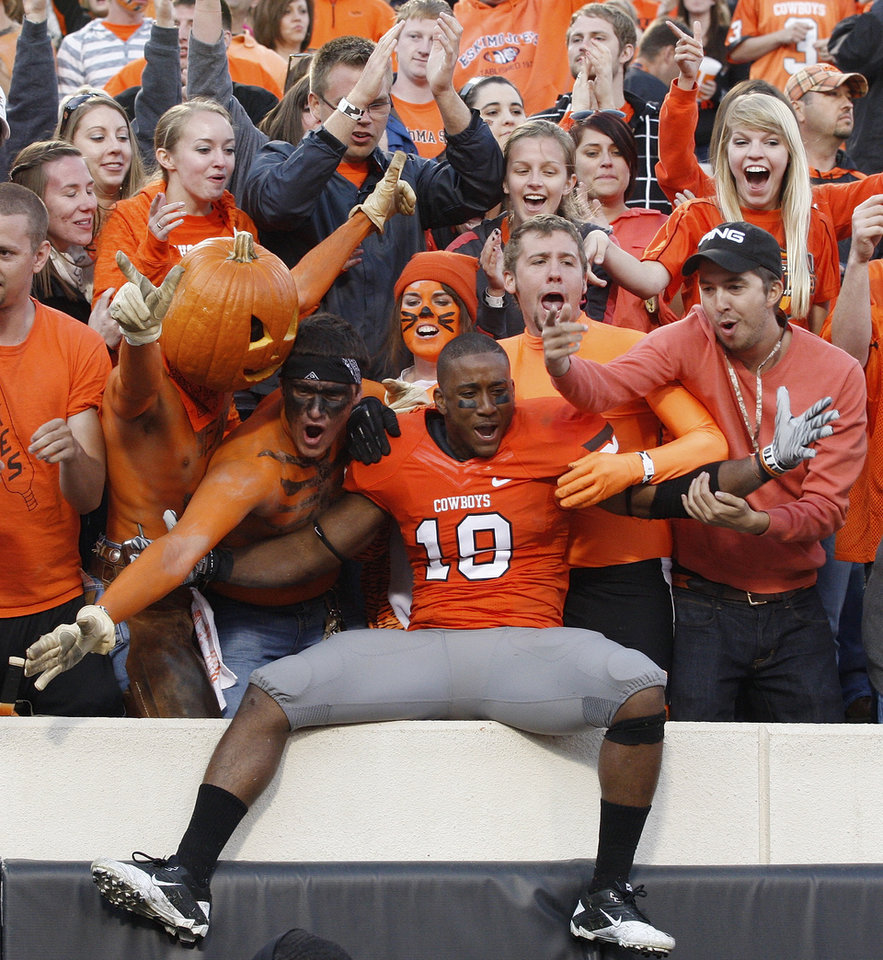 Photo -  Oklahoma State safety Marelle Martin, center, celebrates with fans following a 59-24 victory over Baylor in an NCAA college football game in Stillwater, Okla., Saturday, Oct. 29, 2011. (AP Photo/Sue Ogrocki)