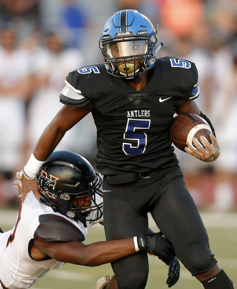 Photo - Deer Creek's Tyler Travis tries to get past Norman's Cedric Seals during a high school football game between Deer Creek and Norman at Deer Creek High School, Friday, Sept. 13, 2019. [Bryan Terry/The Oklahoman]