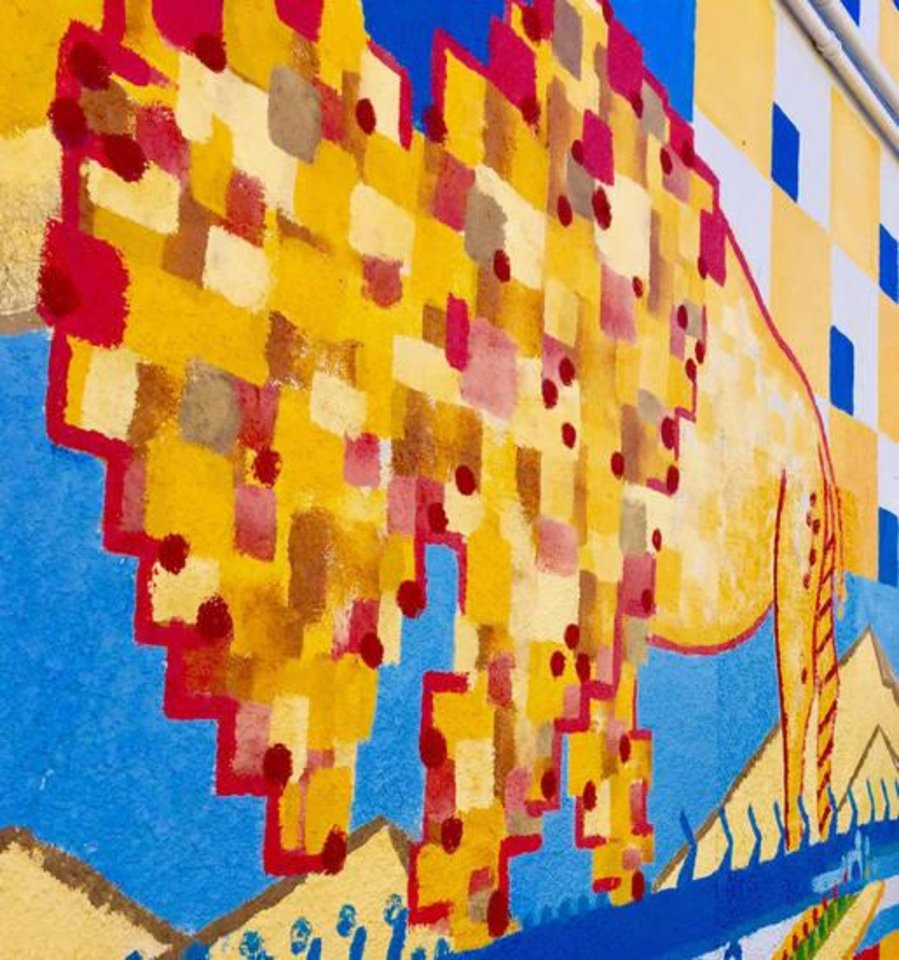 Photo -  A large, colorful buffalo is part of a 60-foot by 13-foot mural being painted on the back of a building seen from Hurd between Broadway and Boulevard. [PHOTO BY DIANA BALDWIN, THE OKLAHOMAN]