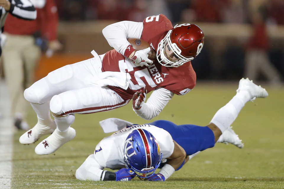 Photo - Oklahoma's Carson Meier (45) is brought down by Kansas' Bryce Torneden (1) during a college football game between the University of Oklahoma Sooners (OU) and the Kansas Jayhawks (KU) at Gaylord Family-Oklahoma Memorial Stadium in Norman, Okla., Saturday, Nov. 17, 2018. Photo by Bryan Terry, The Oklahoman