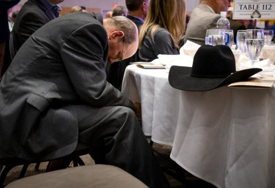 Photo -  The Rev. Tim Turner bows his head in prayer during the Oklahoma Governor's Prayer Breakfast on Tuesday at the National Cowboy and Western Heritage Museum in Oklahoma City. [Chris Landsberger/The Oklahoman]