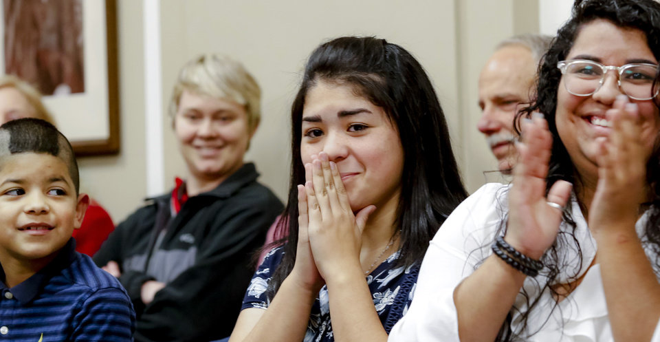 Photo - Children of inmate Juanita Peralta react as Gov. Mary Fallin signs the paperwork that commutes their mother's prison sentence. From left are Dominic Delgado, Alyssa Delgado and Destiny Pinon. During a ceremony Wednesday morning,  Fallin officially commuted the sentences of 21 Oklahoma inmates who were serving sentences 10 years or longer for drug possession and other crimes that now carry lesser punishments following recent reforms approved by voters and state lawmakers. The inmates were assisted through a commutation campaign led by Oklahomans for Criminal Justice Reform. During the emotional event at the Capitol on  Wednesday, Dec. 5, 2018, Fallin signed the commutations one by one for the first group of applicants to make it to her desk after a two-stage review by the Oklahoma Pardon and Parole Board.