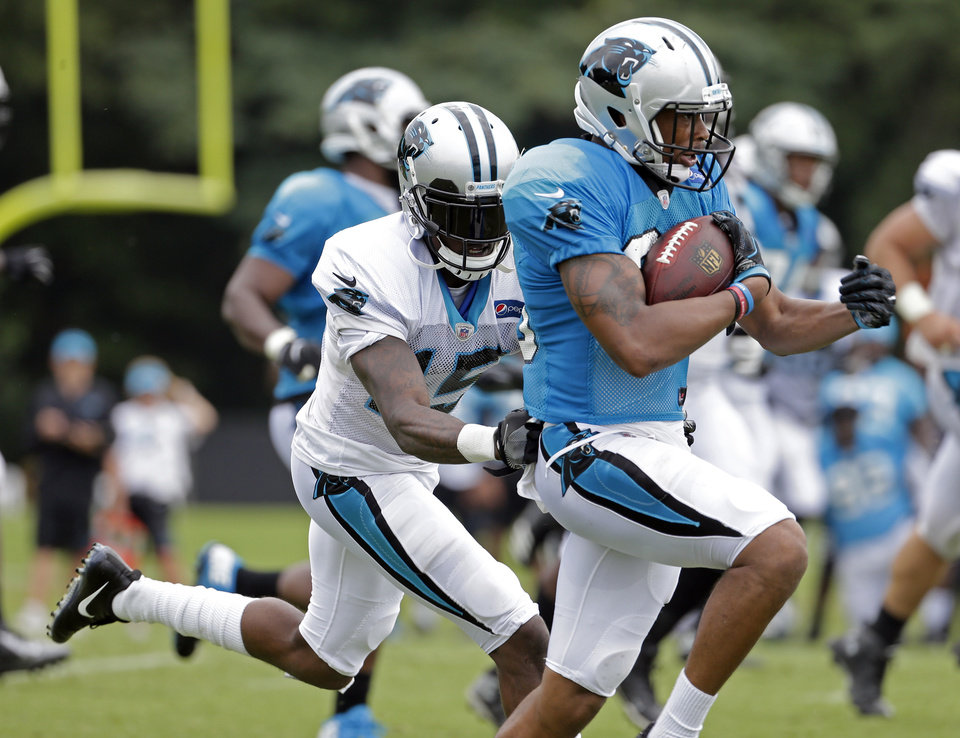 Photo -  Del City's Jeff Richards, right, intercepts a ball intended for former Tulsa University standout Keyarris Garrett, left, during a Carolina Panthers practice in August. [AP PHOTO]